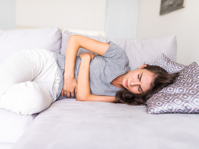 Thumb young woman haviing abdominal pain because menstruation lying couch holding her stomach